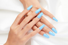 Closeup Shot Of A Female's Hands With Blue Nail Polish On A White Silk Fabric
