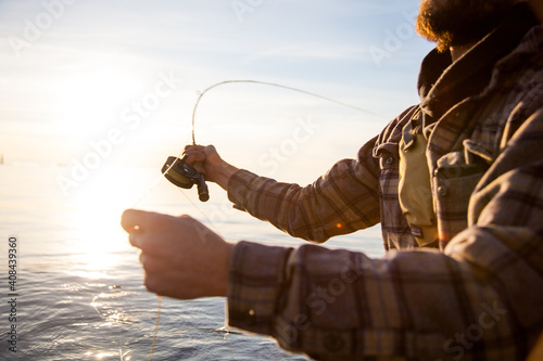 A close up of a fly fisherman wearing a plaid shirt, holding a rod and reel whil Fototapete