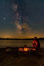 Milky Way Above Lake With A Lantern In A Firepit On The Shoreline And A Person Looking Out Over The Scene
