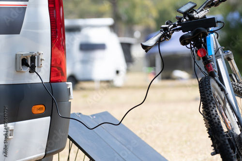 Electric  bicycle battery being charged from RV campervan using solar energy and Fototapet