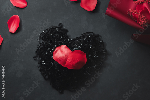 Fototapety, obrazy: A rubber band made a heart shape. With a bouquet of flowers and petals, leaves, red roses Placed on a black background Dark valentines day concept, black day