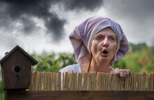 A Curious And Aggressive Neighbor Looks Over A Garden Fence. Dramatic Storm Clouds Are In The Background.