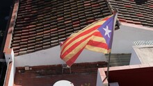 Catalan Flag Flies In The Wind On Sunny Day At The Background Of A Tiled Roof