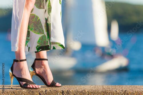 Fotografie, Tablou Woman feet in high heels shoes on sea pier