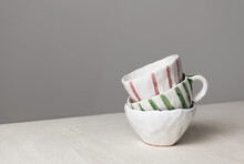 White Ceramic Cups With Colorful Stripes Stack On Table With Linen Tablecloth And Gray Wall Background. Close-up Handmade Ceramic, Horizontal