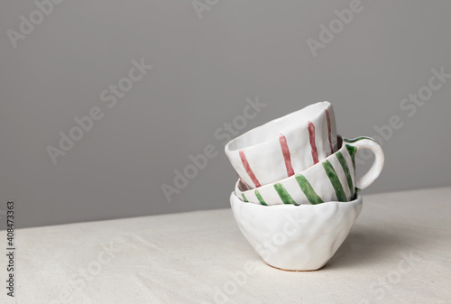 White ceramic cups with colorful stripes stack on table with linen tablecloth and gray wall background Poster Mural XXL