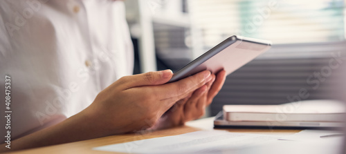 Obraz Businesswoman holding tablet and used to work online on the table at office. - fototapety do salonu