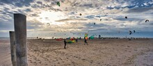 Panoramic View Of People And Colourful Kite Surfers On The Beach During Sunset