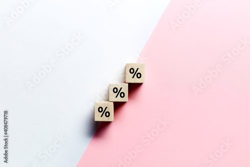 Fotografia Wooden blocks stacking as step stair with percent or percentage symbol on pink and white background