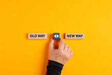 Male Hand Holds A Wooden Cube With Arrow Icon Between The Options Of Old Way Or New Way.