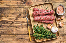 Homamade Raw Mince Meat  Sausages On A Cutting Board. Wooden Background. Top View. Copy Space