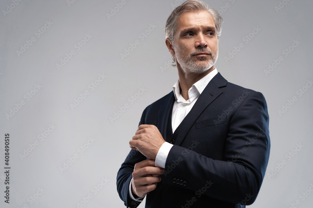 Fototapeta Handsome middle-aged man in suit posing against grey background