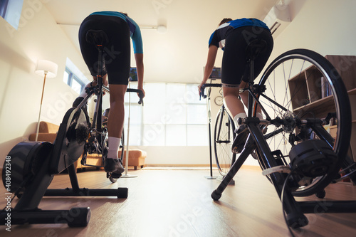 Obraz Asian couple. They are exercising in the home.By cycling on the trainer and play online bike games. - fototapety do salonu