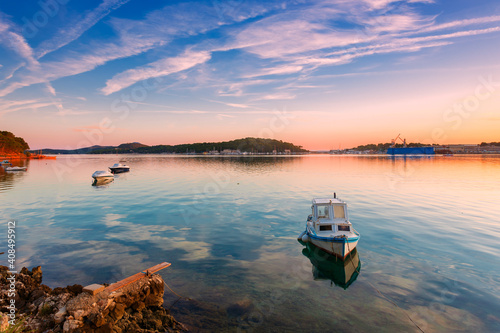 Photo boat moored at the wooden pier in harbour of Losinj town, Croatia