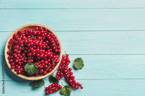 Fototapeta Delicious red currants and leaves on light blue wooden table, flat lay