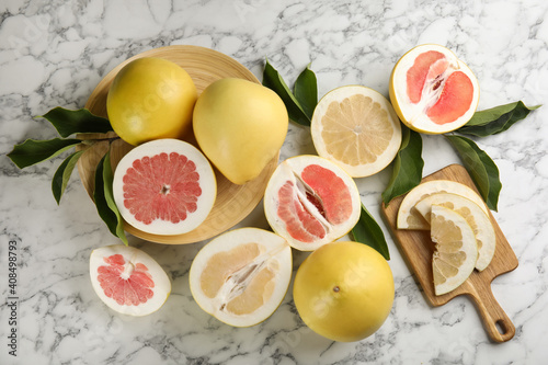 Obraz na plátně Fresh cut and whole pomelo fruits with leaves on white marble table, flat lay
