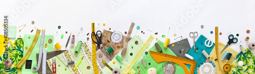 Obraz Spring sewing and home needlework. Panoramic top view on green and yellow pieces of fabric, and sewing accessories on white background. Flat lay, copy space, closeup, banner, mock up - fototapety do salonu
