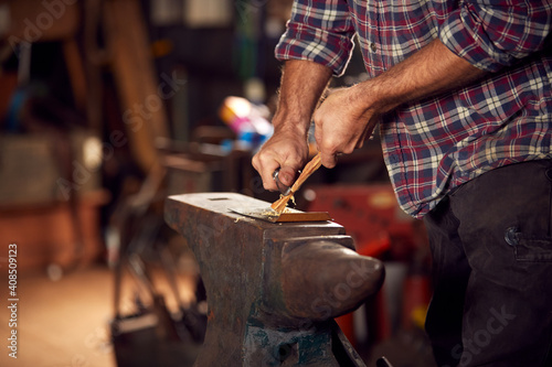 Fotografie, Obraz Close Up Of Male Blacksmith Making Wood Shavings With Knife For Kindling On Anvi