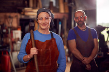 Portrait Of Male And Female Blacksmiths Holding Tools Standing In Forge