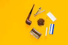 Set Of Accessories For Smoking Tobacco Top View, Smoking Pipe, Cigarette, Rolling Machine And Paper. Isolated Flat Lay On Yellow Background