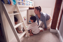 Asian Mother With Children Having Fun Playing With Toys In Bedroom Together