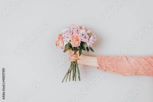 Obraz In the hand a bunch of flowers against a white background. Valentine's day gift. Present a bouquet of flowers, Woman day gift, 8 march - fototapety do salonu