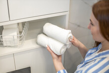 Woman's Hands Neatly Putting Or Displaying A Clean Rolled Up White Towels Made From Organic Cotton.