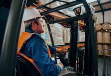 Side Shot Of A Male Worker Driving The Forklift Truck In The Warehouse