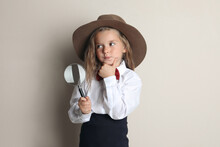 Cute Little Child In Hat With Magnifying Glass Playing Detective On Beige Background
