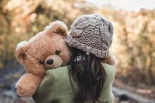 Little Girl Hugs Her Bear On A Background Of Nature, Autumn, Durba.