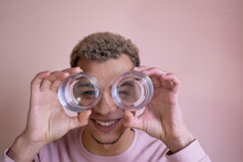 Laughing Young American Man Holding Transparent Glasses And Looking Through Them Like Binoculars; Lifestyle Photo Of A Handsome Black Man