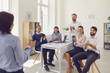 Leinwandbild Motiv Business people coworkers sitting in office and applauding standing woman colleague after successful presentation