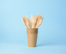 Wooden Fork And Brown Paper Cup On A Blue Background