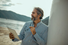 Portrait Of Retirement Handsome Senior Man Using Tablet Computer On Seafront
