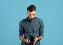 Poverty And Unemployment. Desperate Young Man Showing Empty Wallet With No Money Over Blue Studio Background