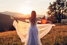 Beautiful Bride Dancing In Blue Wedding Dress In Mountains At Sunset. Woman Enjoys Landscape Holding Gown