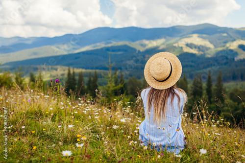 Obraz Traveling in spring Ukraine. Trip to Carpathian mountains. Woman tourist relaxing in flowers admiring view - fototapety do salonu