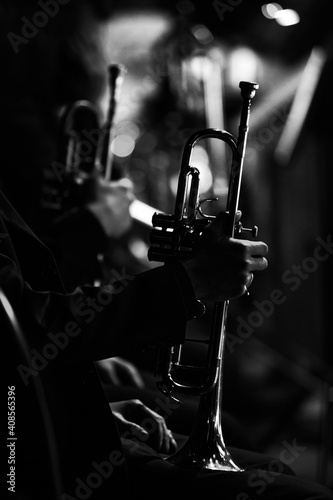 Silhouette of a trumpet in the hands of a musician in an orchestra in dark color Fototapeta