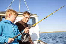 Male Fisher Teaching Boy Fishing On Boat