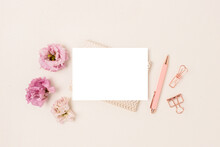 Blank Paper Card Mockup, Stationery And Eustoma Flowers On A Beige Background. Feminine Workspace With Copyspace. Cute Springtime Concept.