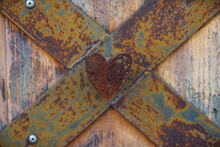 Rusted Metal Heart In Focus With Blurred Rusted Cross And Rustic Wood Background