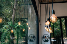 Illuminated Light Bulbs Hanging By Window At Home