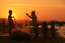 Fishermen Standing By Fishing Net Against Sky During Sunset