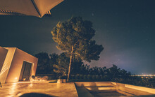 Trees Outside House Against Sky At Night
