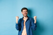 Leinwandbild Motiv Image of happy man celebrating success, shouting yes and shaking clenched fists, achieve goal and triumphing, winning and dancing, standing on blue background