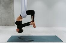 Full Length Of Ballet Dancer Hanging On Textile At Gym