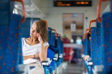 Young Woman Sitting In The Train After A Day Of Work . Train Passenger Traveling Sitting Relaxed And Enjoying The Ride