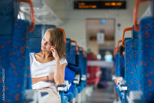 Fototapeta Young woman sitting in the train after a day of work