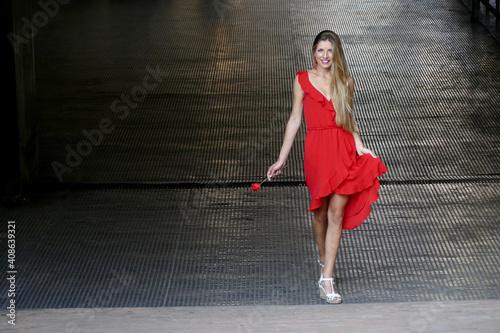 Obraz na plátně Bellissima ragazza bionda sorridente con vestito rosso