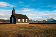 Black Wooden Budakirkja Church Against Snowcapped Mountains, Budir, Snaefellsness Peninsula, Iceland